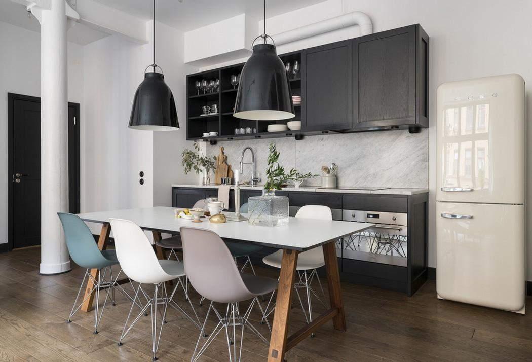 Черный фасад кухни разбавили белым столом с цветными стульями
