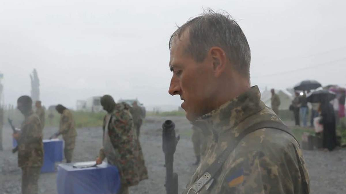 Украинский солдат принимает присягу под дождем
