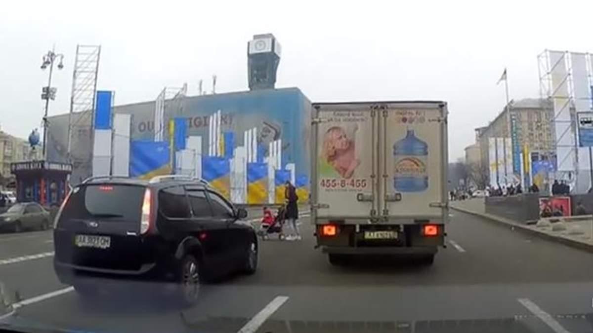 Жінка із дитячим візочком переходить дорогу у Києві