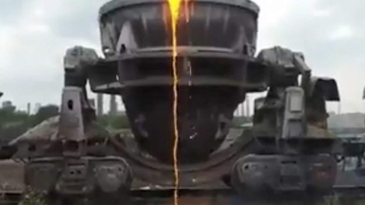 На кадрах видно, как из ковша, который движется в составе железнодорожных прицепов, льется разгоряченная лава