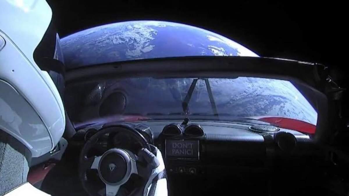 Tesla на фоні Землі у космосі