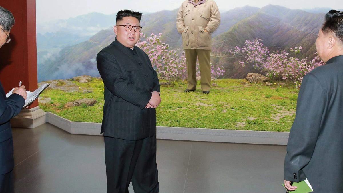 Ким Чен Ын на фоне портрета отца