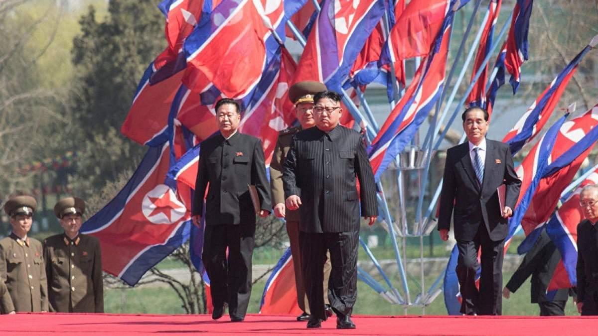 Ким Чен Ын на фоне флагов КНДР