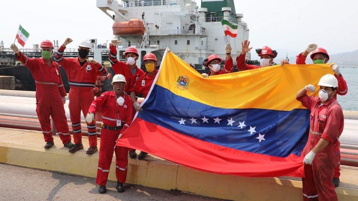 Працівники з прапорами Ірану та Венесуели