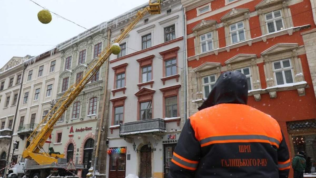 Працюють альпіністи: у Львові активно борються з нависанням буруль та снігу на дахах – фото