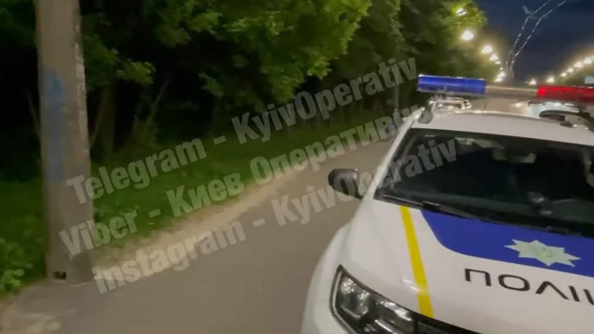 Лежить людина, а біля літають мухи: у Києві в кущах біля АЗС виявили мертву голу жінку – відео