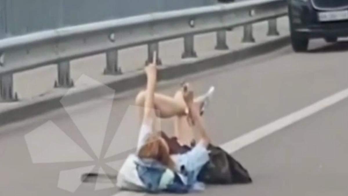 В Киеве возле Гидропарка девушка разлеглась посреди дороги