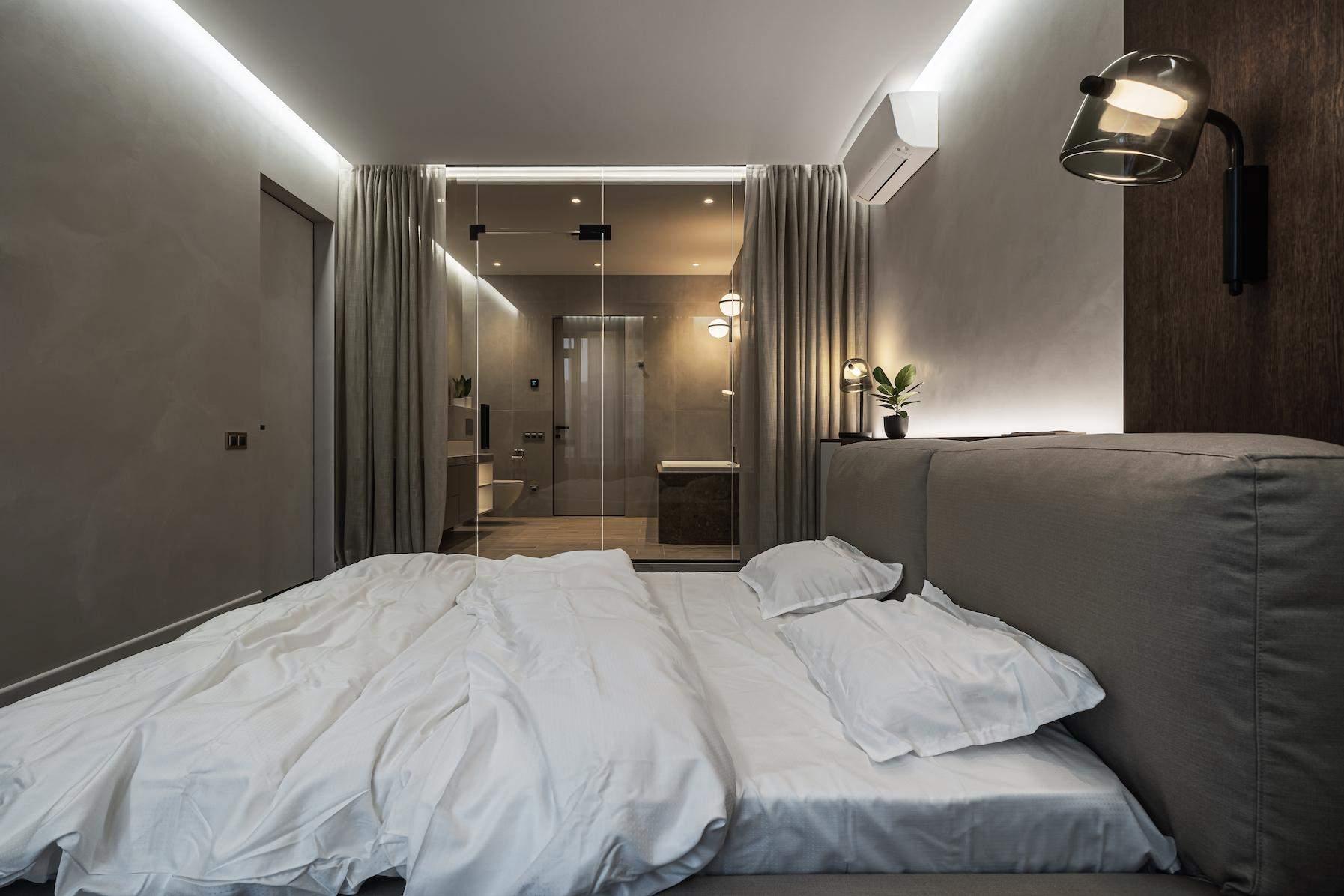 Прозора стіна в ванну кімнату нагадує вікно і візуально розширює простір спальні