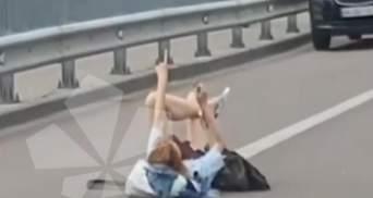 У Києві біля Гідропарку дівчина розляглася посеред дороги та махала водіям руками: відео