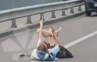 В Киеве возле Гидропарка девушка разлеглась посреди дороги и махала водителям руками: видео