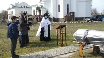 Труна в мішку, гробарі – в спецкостюмах: як поховали монаха Нектарія з лаври