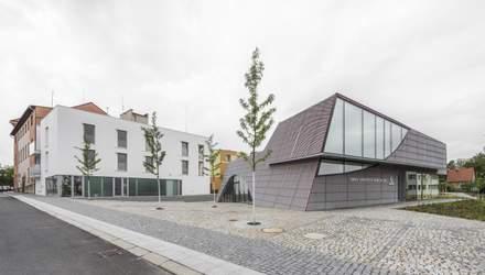"""Білосніжні стіни та дерев'яні лави: фото культурного центру з Чехії, який """"вгруз"""" у землю"""