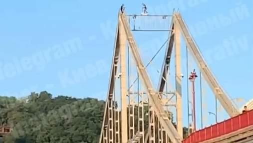 На висоті 32 метри: у Києві хлопець катався на самокаті балкою пішохідного мосту – відео