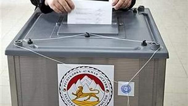 Виборець вкидає бюлетень в урну для голосування