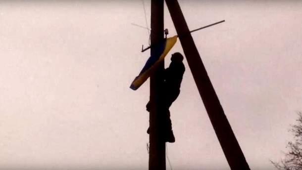 Украинский воин устанавливает флаг Украины на оккупированной территории