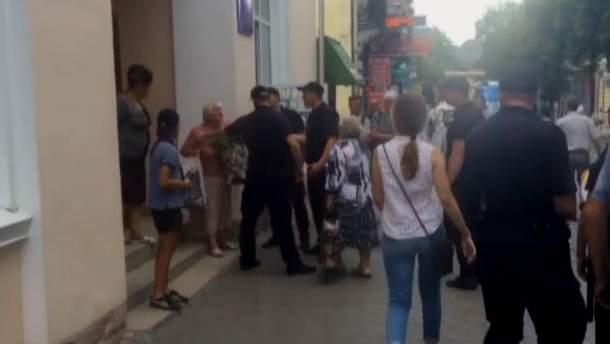 Полицейские забирают пенсионерку в участок