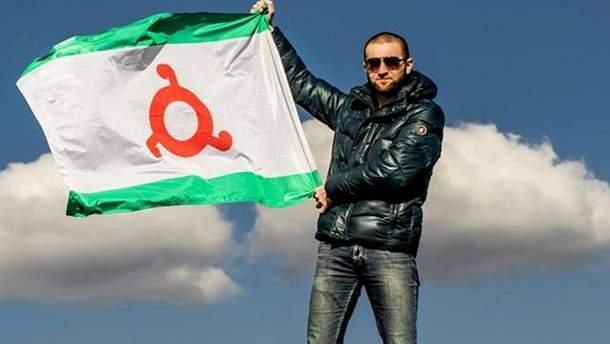 Мужчина держит в руках флаг Ингушетии