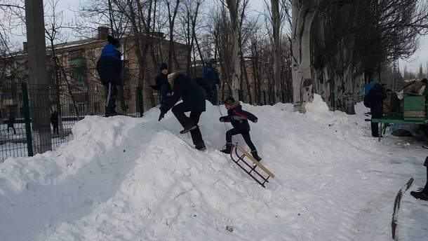 Дети веселятся и катаются на санках в Авдеевке