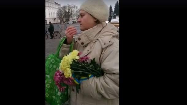 Жінка забрала квіти, які принесли для загиблих бійців