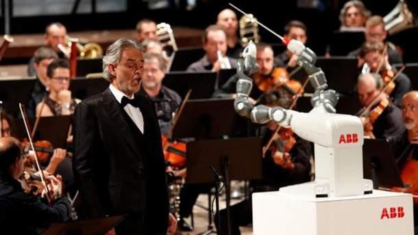 Робот Yumi дирижирует оркестром с тенором Андреа Бочелли