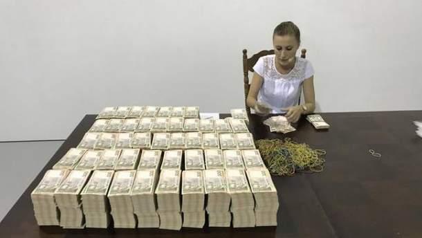 Дівчина перераховує 1 мільйон доларів у гривнях