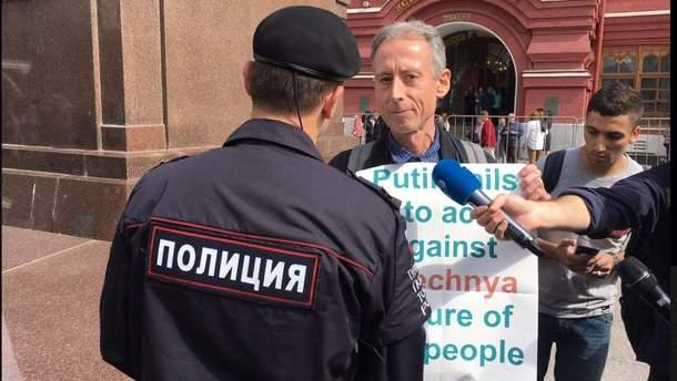 """Чоловік прийшов до Кремля із плакатом, на якому писало: """"Путін ніяк не перешкоджає катуванню геїв у Чечні""""."""