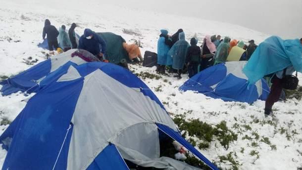 У дощовиках посеред засніжених гір: рятувальники добралися до дитячого табору в Карпатах (фото)