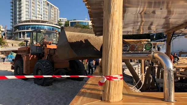 На кадрах видно, как бульдозер сносит деревянный пляжный комплекс с барной стойкой и холодильниками внутри