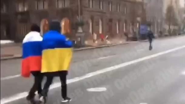 В Киеве неизвестные прогуливались с флагами Украины и России: видео