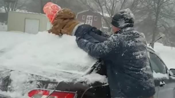Отец очистил машину от снега собственным ребенком и прославился