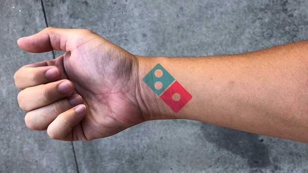 Татуировка с логотипом Domino's Pizza