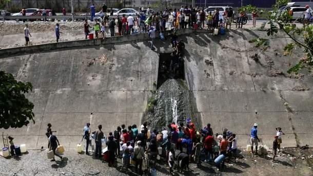 Люди набирают остаточную воду из водопровода