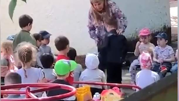 У Росії вихователька поставила дитину на коліна і змусила її цілувати землю