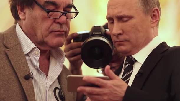 Стоун та Путін уважно вивчають щось на екрані смартфону
