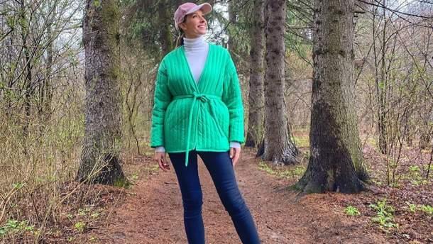 Катя Осадчая показала яркий образ в трендовой зеленой куртке: атмосферное фото из леса