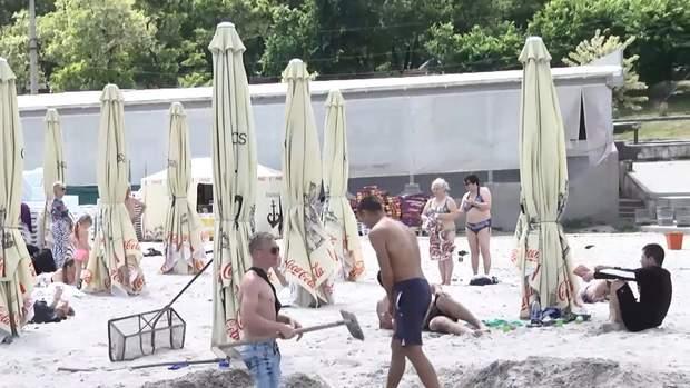 Працівники пляжу закопують сміття