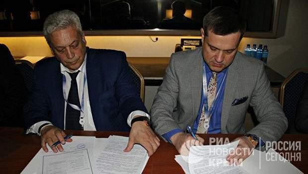 Дмитро Сташків (праворуч)підписує контракт / Фото РиаНовости