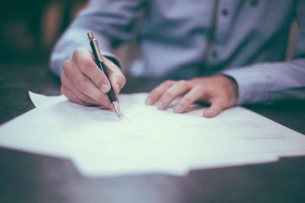 Людина підписує аркуш, бюрократія