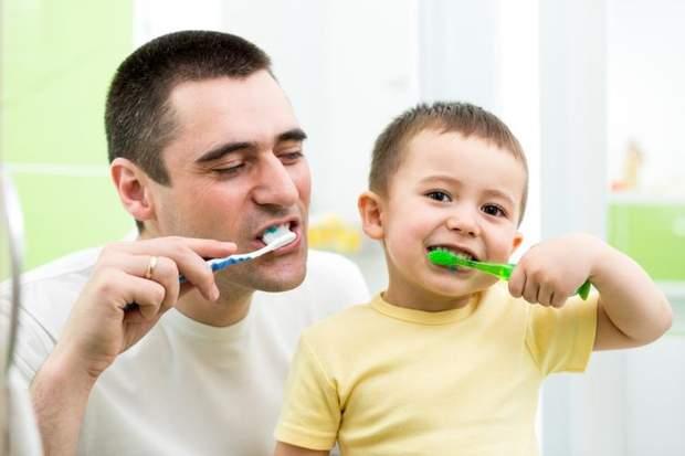 Дитина чистить зуби з татом