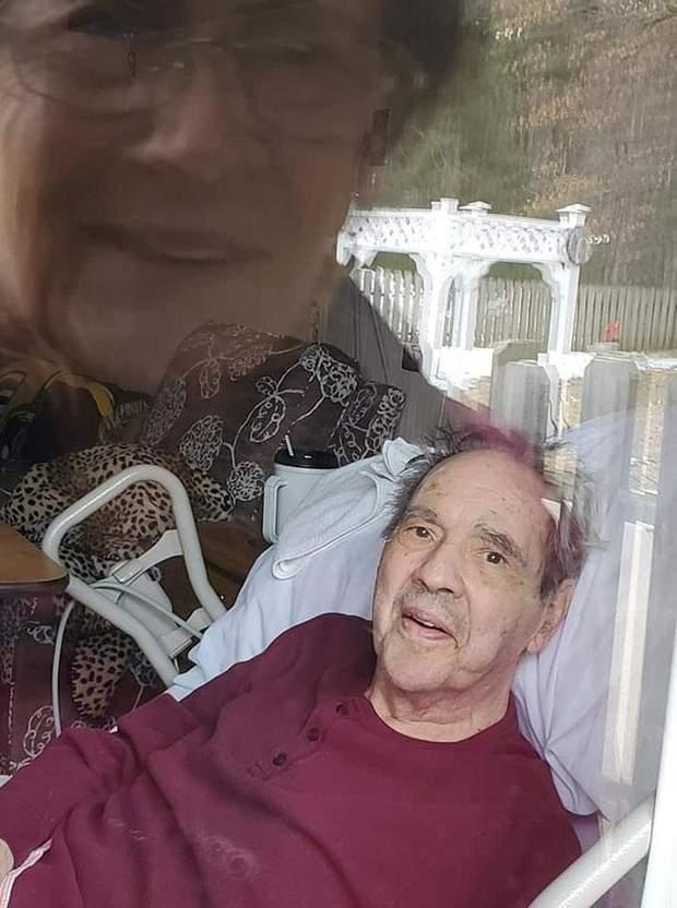 Чоловік і дружина дивляться один на одного через вікно будинку престарілих