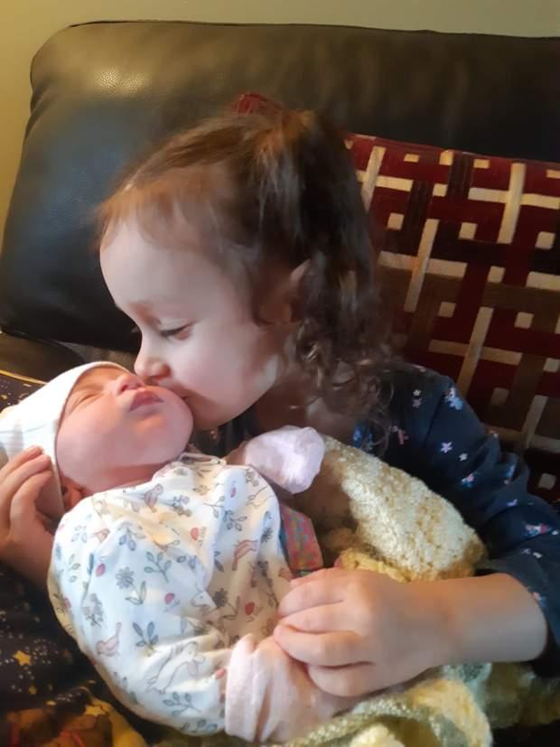 Дівчинка Емілія цілує братика
