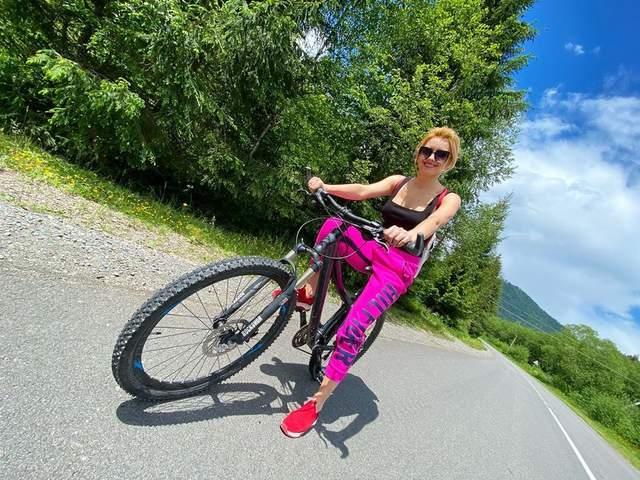 В брюках цвета фуксии и черном топе: Ирина Федишин покаталась на велосипеде в Карпатах – фото