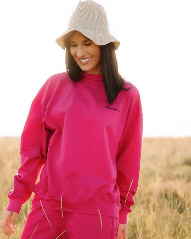 Маша Єфросиніна у рожевому костюмі серед поля
