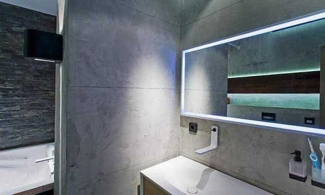 Стены в ванной комнате отделаны бетоном