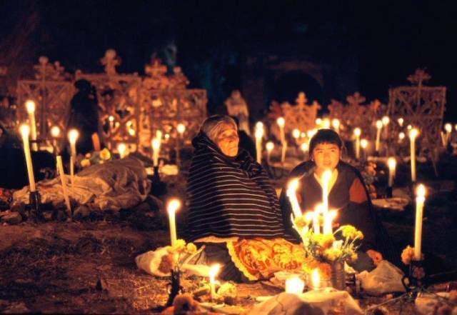 Старші люди спокійно сидять на могилі та спілкуються з померлими