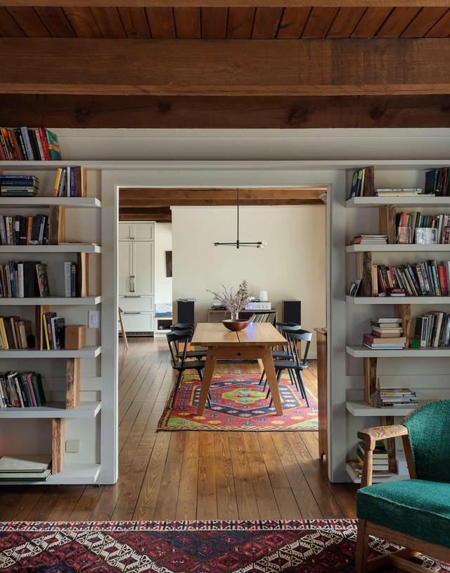 В доме много открытых стеллажей с книгами и другими вещами