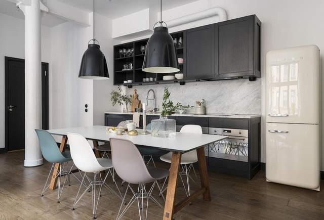 Чорний фасад кухні розбавили білим столом з кольоровими стільцями