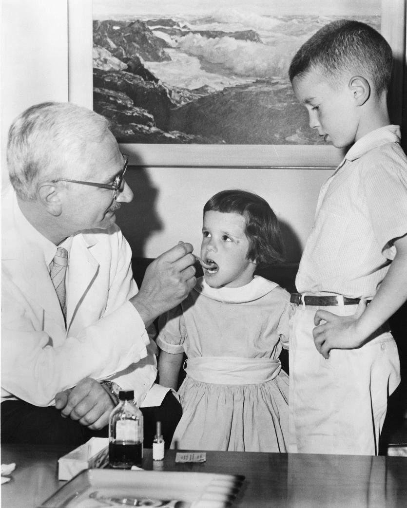Альберт Сабін демонструє, як дітям роблять пероральну вакцину проти поліомієліту